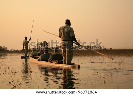 Sailing in traditional mokoro in The Okavango Delta, Botswana - stock photo