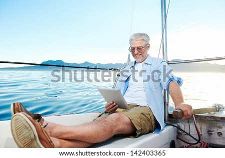 sailing man reading tablet computer on boat with modern technology and carefree retired senior successful lifestyle - stock photo