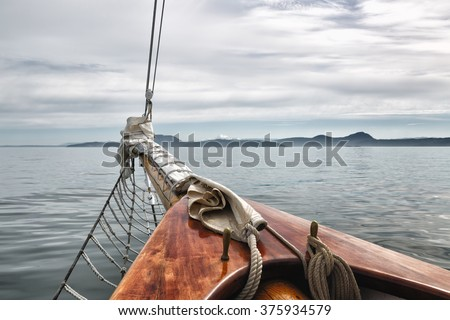 Sailing on a big vintage wooden schooner in the San Juan Islands, Washington State, USA. Close up view of the front of the boat. Mt. Rainier in the distance. Copy space.  - stock photo