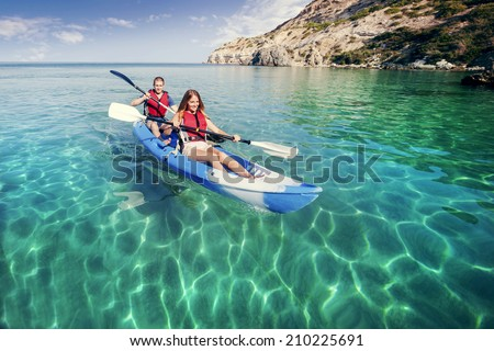 Sailing on the sea kayaking. Young happy couple traveling by kayak. Activities on the water.  - stock photo