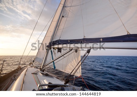 Sailing on yacht at sunset - stock photo