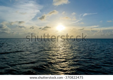 Sailing out on the ocean, an island is seen in the far left distance during a warm and beautiful sunset over the Caribbean Sea.  - stock photo