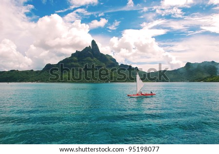 Sailing  over the turquoise-color lagoon , with the Otemanu mountain behind the scene . - stock photo