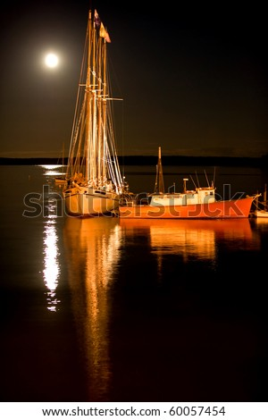 Sailing ship and fishing boat in Bar Harbor, Maine in the moonlight - stock photo