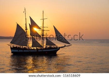 Sailing ship at sunset - stock photo