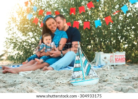 sailing ship in the foreground of family sitting on the beach - stock photo
