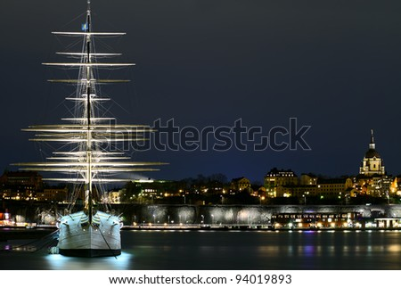 Sailing ship is in foreground  of Skeppsholmen islands at night, Stockholm, Sweden. - stock photo