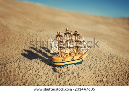 Sailing ship model on sand under blue sky - stock photo