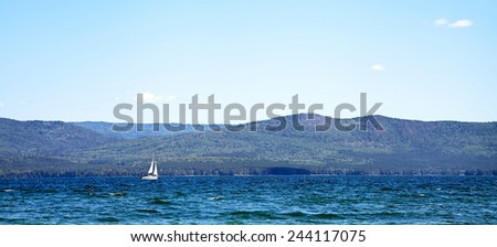 sailing ship on a mountain lake in good weather on a background of blue sky. nature background. yachting - stock photo