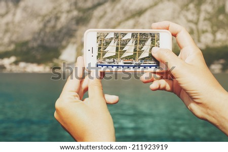 Sailing ship seen through lens of a mobile phone - stock photo