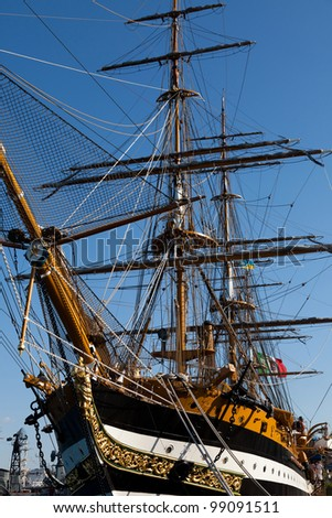 Sailing ship with tall masts against a blue sky - stock photo