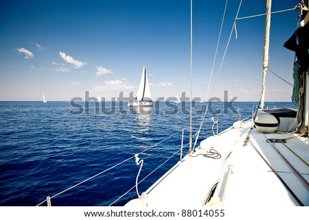 Sailing ship yacht with white sail in open sea - stock photo