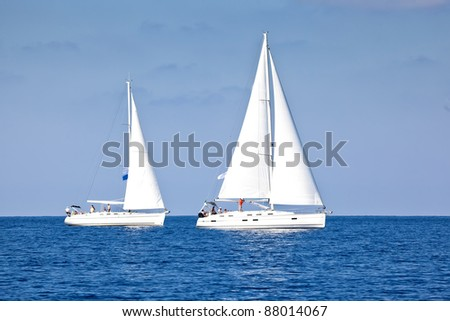 Sailing ship yachts with white sails at the open sea - stock photo