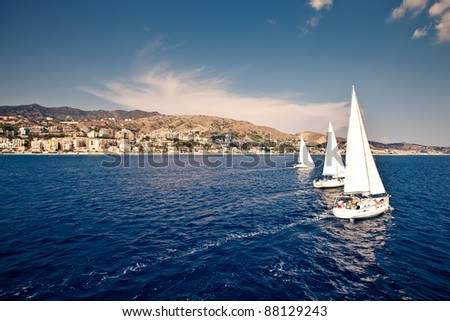 Sailing ship yachts with white sails in a row. Aerial view - stock photo