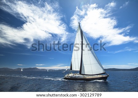 Sailing ship yachts with white sails in the open Sea. Luxury lifestyle. - stock photo