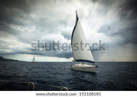 Sailing ship yachts with white sails in the sea in stormy weather - stock photo