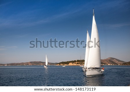 Sailing ships yacht with white sails in a row