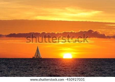 Sailing sunset is a sailboat moving along the water as the sun is going down on the ocean horizon.