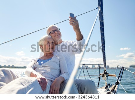 sailing, technology, tourism, travel and people concept - happy senior couple taking selfie with smartphone on sail boat or yacht deck floating in sea - stock photo