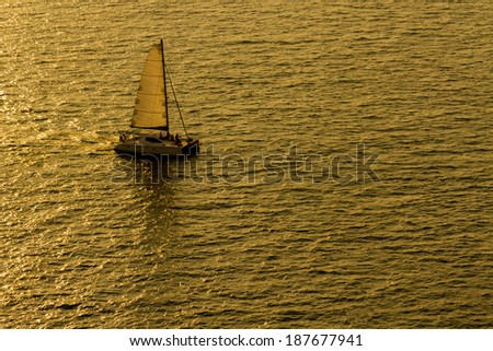 Sailing yacht boat on golden tropical sea,sunset in Thailand. - stock photo