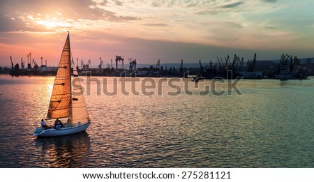 Sailing yacht enters Varna harbor at the sunset. Black Sea, Bulgaria. Stylized photo with tonal correction photo filter - stock photo