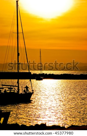 Sailing yacht on sunset in sardegna, vertical - stock photo