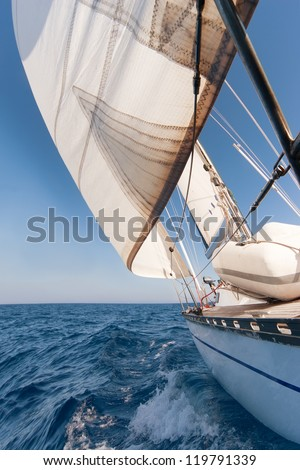 Sailing yacht on the race in blue sea - stock photo