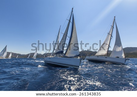 Sailing yacht race. Sailing ships yachts with white sails in the open sea. - stock photo
