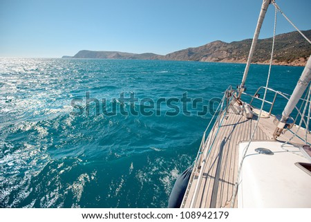 Sailing yacht sailing along the mountainous coast - stock photo