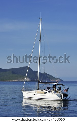 Sailing yacht with two people approaching a remote Greek island in early morning - stock photo