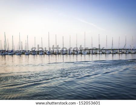 Sailing Yachts in marina at sunset - stock photo
