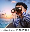 Sailor boy looks at horizon from binoculars - stock photo