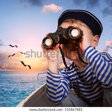 Sailor boy looks at horizon from binoculars - stock photo