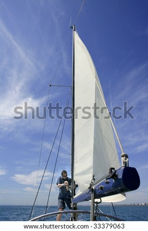 Sailor in sailboat rigging the sails over sunny summer blue sky - stock photo