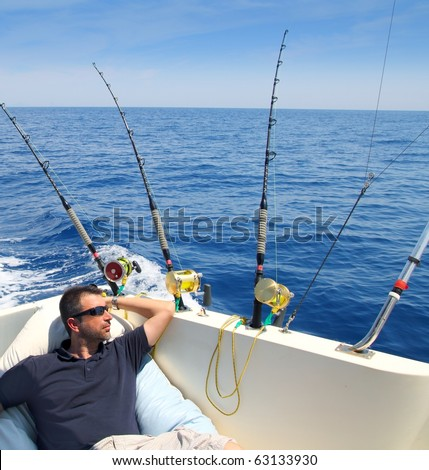 Sailor man fishing resting in boat summer vacation blue sea - stock photo