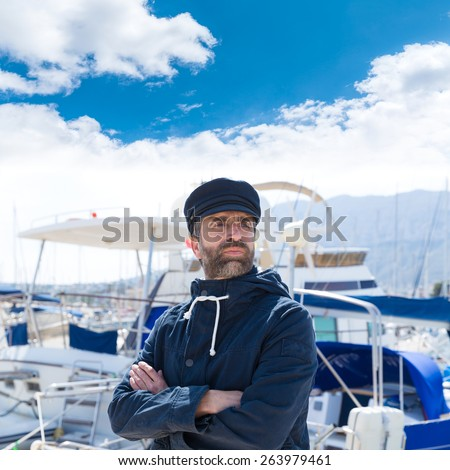 Sailor man in marina port with boats background and blue cap - stock photo