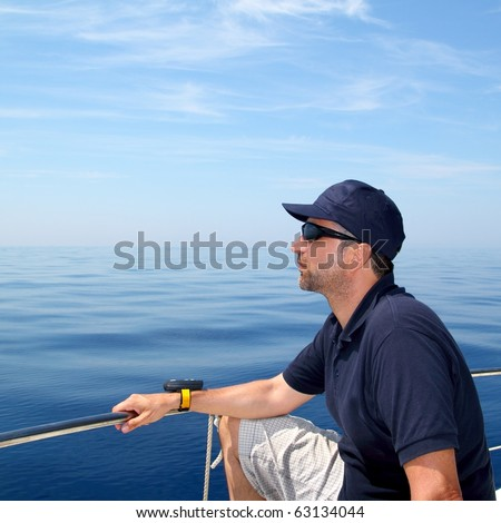 Sailor man sailing boat blue calm ocean water Mediterranean sea - stock photo