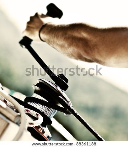 Sailor pulling rope, outdoor activities, sailboat sport race, man in action - stock photo