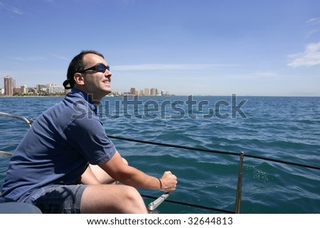 Sailor sailing blue tropical sea on sailboat in summer vacation - stock photo