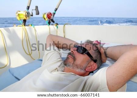 Sailor senior fisherman relax on boat fishing deep sea - stock photo