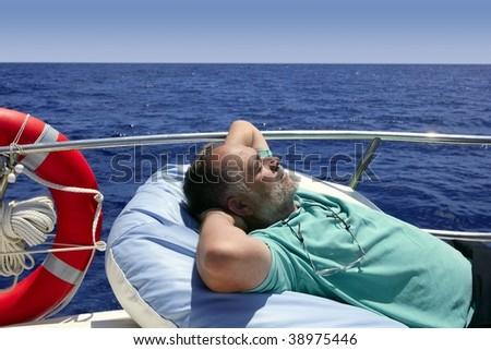 Sailor senior man having a rest on summer boat over blue ocean - stock photo
