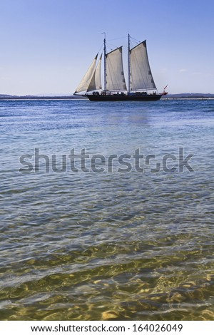 sailor tall ship in the pacific ocean captured distant from beach on clear sea water vertical view - stock photo