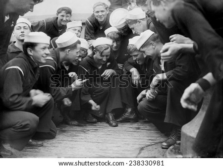 Sailors playing a dice game on the New York, original title: 'Shooting craps on New York', photograph circa 1900s-1930s - stock photo