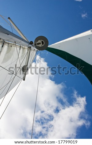 Sails, GPS and radar of a catamaran boat with a deep blue sky and white cloud