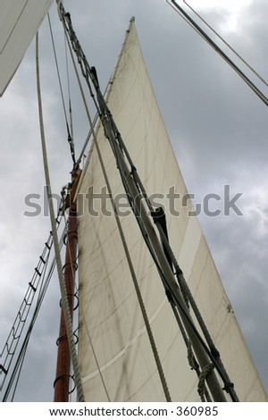 Sails of a boat with clouds in the background.