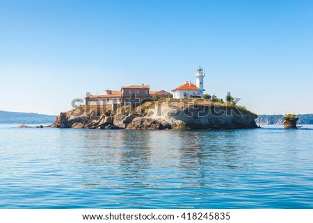 Saint Anastasia Island in Burgas bay, Black Sea, Bulgaria. Lighthouse tower and old wooden buildings on rocky coast
