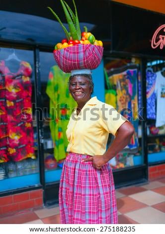 SAINT ANN, NORTH COAST OF JAMAICA - APRIL 2, 2008: Local fruits trader is greeting buyers on a market place. - stock photo
