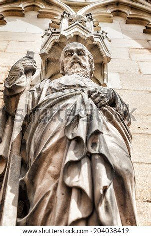 Saint Bartholomew shot from below, focus on face of the statue at the west front of Lichfield Cathedral. Staffordshire, England, Britain. - stock photo