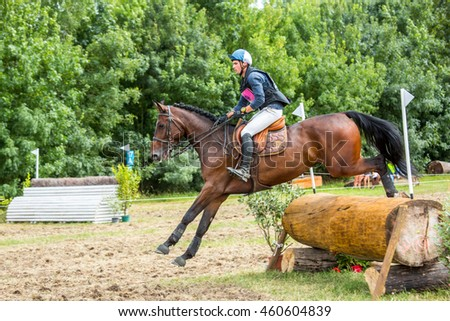 Saint Cyr du Doret, France - July 29, 2016: Horseman riding horse over an obstacle on cross country event