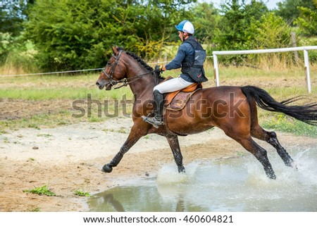 Saint Cyr du Doret, France - July 29, 2016: Rider crossing water jump galloping at a cross country manisfestation
